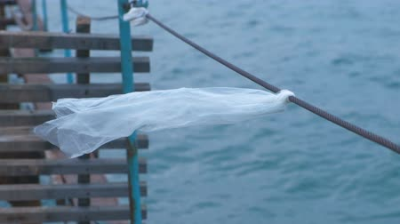 leftover : Plastic bag is tied to the cable of the sea pier.