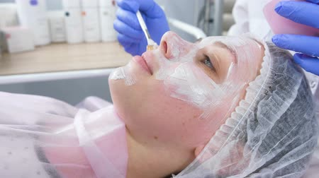bőrápolás : Beautician puts a white mask on the womans face with a brush. Hands of a cosmetologist in blue rubber gloves. Facial treatments. Side view. Stock mozgókép