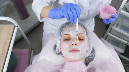 sterility : Beautician puts a white mask on the womans face with a brush. Hands of a cosmetologist in blue rubber gloves. Facial treatments. Top view.