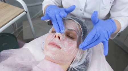 sterility : Beautician rolls the mask on the womans face massage movements. Cosmetologist facial treatment.