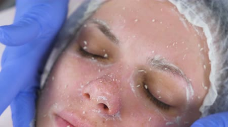 sterility : Beautician rolls the mask on the womans face massage movements. Cosmetologist facial treatment. Close-up. Stock Footage