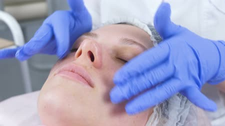 sterility : Beautician puts the cream on the womans face. Cosmetologist facial treatment. Close-up. Stock Footage