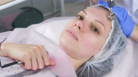 stimulating : Cosmetologist makes a micro-current procedure for the face of a young woman. Face close-up.