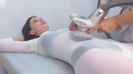 целлюлит : Cosmetologist makes a woman in nylon suit lpg massage on the tummy. Belly and hands close-up.