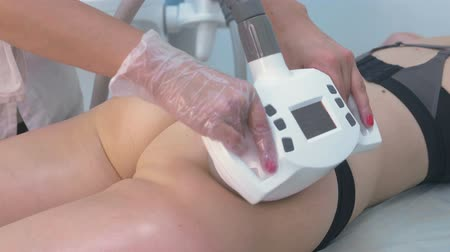 booty : Ultrasound cavitation body contouring treatment. Woman getting anti-cellulite and anti-fat therapy for buttocks in beauty salon. Hands close-up. Stock Footage