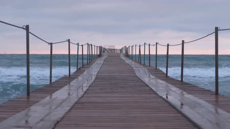 tir : Waves splashes through the wooden pier in the sea. Beautiful seascape at sunset. Stock Footage