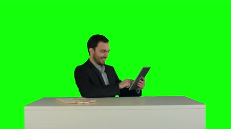 ключ : Business man working on digital tablet on his table in his office on a Green Screen, Chroma Key. Professional shot on BMCC RAW with high dynamic range. You can use it e.g in your commercial video, business video, office theme.