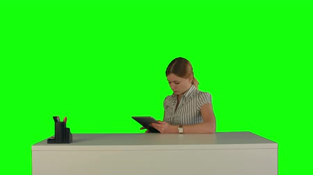 verimlilik : Business woman sitting in her office using a tablet computer on a Green Screen, Chroma Key. Professional shot on BMCC RAW with high dynamic range. You can use it e.g in your commercial video, business video, office theme. Stok Video