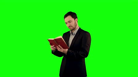 rubi : University student with book on laptop on a Green Screen, Chroma Key. Professional shot on BMCC RAW with high dynamic range. You can use it e.g in your commercial video, business video, office theme. Stock Footage