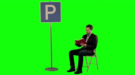 pólos : Young man reading a book near parking sign on a Green Screen, Chroma Key. Professional shot on BMCC RAW with high dynamic range. You can use it e.g in your commercial video, business video, office theme. Stock Footage