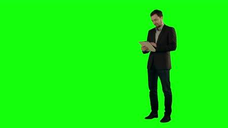 tuşları : Happy Young Man Using Digital Tablet  on a Green Screen, Chroma Key. Professional shot on BMCC RAW with high dynamic range. You can use it e.g in your commercial video, business video, office theme.