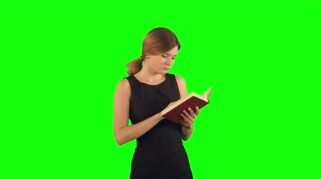 chroma key background : Young girl with book on laptop on a Green Screen, Chroma Key. Professional shot on BMCC RAW with high dynamic range. You can use it e.g in your commercial video, business video, office theme. Stock Footage