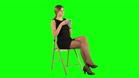 chroma key background : A young attractive woman with a cup of coffee or tea on laptop on a Green Screen, Chroma Key.  Professional shot on BMCC RAW with high dynamic range. You can use it e.g in your commercial video, business video, office theme.