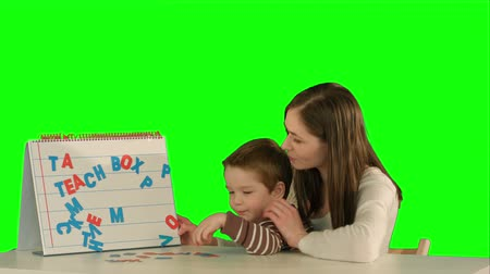 klíčové slovo : Mother and son make word Mama on the desk on a Green Screen, Chroma Key. Professional shot on BMCC RAW with high dynamic range. You can use it e.g in your commercial video, family video, music video.