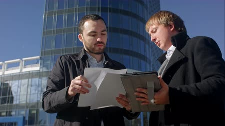 Two young businessmen discussing document. Professional shot on BMCC with high dynamic range. You can use it e.g in your commercial video, business or office video, reporting, presentation, music video, clips.
