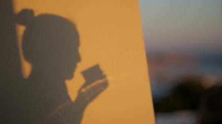 rivera : shadow silhouette of a girl drinking beverage from glass portugal evening sea viewProfessional shot on DSLR with high dynamic range. You can use it e.g in your video, documentalistic, reporting, presentation, music video, commercial video.