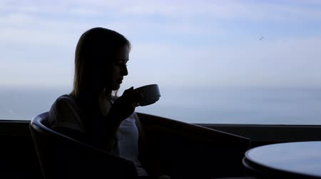 созерцать : silhouette of young beautiful girl sits in a cafe with panoramic views of sea. Morning with a cup of coffe, tea, drinking, thinking beholdingProfessional shot on DSLR with high dynamic range. You can use it e.g in your video, documentalistic, reporting, p