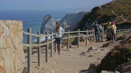 созерцать : tourist girl beholding ocean view with rocs in Cabo da Roca, atlantic border of europe september portugalProfessional shot on DSLR with high dynamic range. You can use it e.g in your video, documentalistic, reporting, presentation, music video, commercial