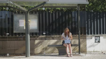 otobüs : Lonely young woman waiting at glass bus stop in skirt with smart phone and handbag, summertimeProfessional shot on DSLR with high dynamic range. You can use it e.g in your video, documentalistic, reporting, presentation, music video, commercial video. Stok Video