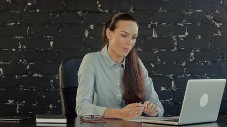 использование : Young Businesswoman Videochatting With Colleagues On Computer In Office. Professional shot on BMCC with high dynamic range. You can use it e.g in your commercial video, business or office video, reporting, presentation, music video, clips. Стоковые видеозаписи