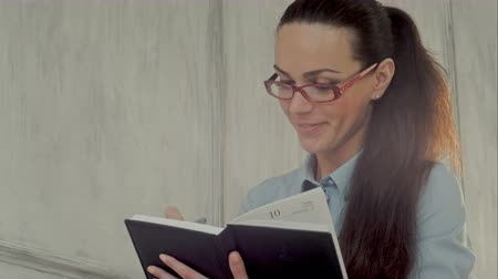 szemüveg : Smiling businesswoman in glasses with notepad. Professional shot on BMCC with high dynamic range. You can use it e.g in your commercial video, business or office video, reporting, presentation, music video, clips. Stock mozgókép