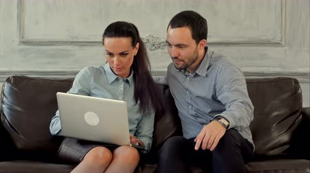 couro : Businessman and business woman sitting at office lobby on leather sofa working with laptop. Professional shot on BMCC with high dynamic range. You can use it e.g in your commercial video, business or office video, reporting, presentation, music video, cli Vídeos