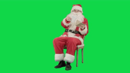 záradék : Santa Claus sitting on chair with letters in hands on a Green Screen, Chroma Key. Professional shot on BMCC RAW with high dynamic range. You can use it e.g in your commercial video, christmas holiday video, santa claus theme, dance party.