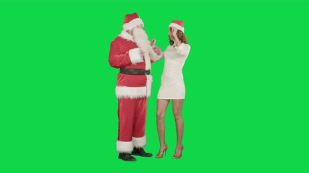 ключ : Christmas woman with santa claus dancing on a Green Screen, Chroma Key. Professional shot on BMCC RAW with high dynamic range. You can use it e.g in your commercial video, christmas holiday video, santa claus theme, dance party.