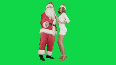 santa : Christmas girl with santa claus dance on a Green Screen, Chroma Key. Professional shot on BMCC RAW with high dynamic range. You can use it e.g in your commercial video, christmas holiday video, santa claus theme, dance party. Stock Footage