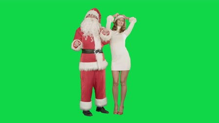 senhora : Beautiful happy woman dancing with Santa Claus on a Green Screen, Chroma Key. Professional shot on BMCC RAW with high dynamic range. You can use it e.g in your commercial video, christmas holiday video, santa claus theme, dance party.