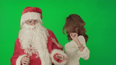 vysoká klíč : Beautiful christmas woman dancing with Santa Claus on a Green Screen, Chroma Key. Professional shot on BMCC RAW with high dynamic range. You can use it e.g in your commercial video, christmas holiday video, santa claus theme, dance party.