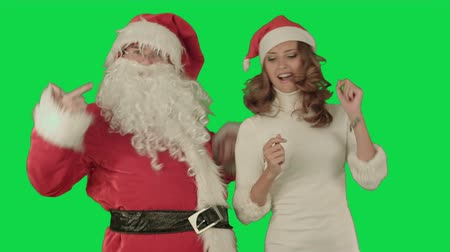 serbest : Santa claus dance with Attractive Christmas lady on a Green Screen, Chroma Key. Professional shot on BMCC RAW with high dynamic range. You can use it e.g in your commercial video, christmas holiday video, santa claus theme, dance party. Stok Video