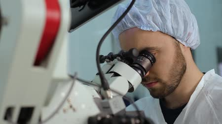 laboratorní plášť : close-up of Man using a big microscope system in a medical laboratory Dostupné videozáznamy