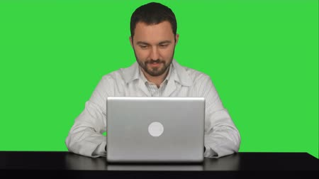 profi : Smiling male doctor sitting at table with laptop on a Green Screen, Chroma Key. Professional shot on BMCC RAW fith high dynamic range. You can use it e.g in your commercial video, commercial video, medical ,video about clinic, doctor, health, hospital, me Stock mozgókép