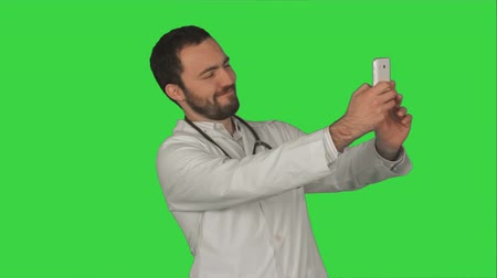 chroma key background : Doctor or medic taking a selfie with front camera of smartphone on a Green Screen, Chroma Key. Professional shot on BMCC RAW fith high dynamic range. You can use it e.g in your commercial video, commercial video, medical ,video about clinic, doctor, healt
