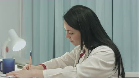 przychodnia : Tired female doctor sits in a medical office in the clinic, drinks glass of water and writes diagnose of patient