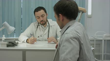kule : Male bearded doctor in clinic consult sick client with legs injury.