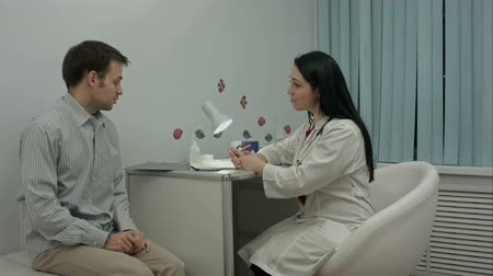 complaints : Patient in a medical office tells the doctor about his health complaints Stock Footage