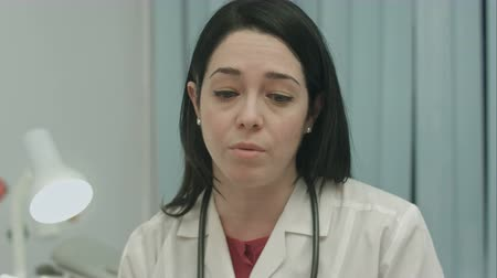 médicos : Serious female doctor talking about a illness and result at modern hospital indoors, close-up