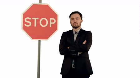 útkereszteződés : A businessman holding a stop sign on laptop on white background isolated.  Professional shot on BMCC RAW with high dynamic range. You can use it e.g in your commercial video, business video, office theme.
