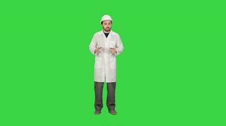 tuşları : Architect in helmet talking to camera on a Green Screen, Chroma Key.