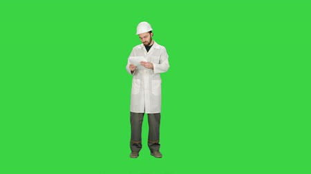 planları : Building Architect Master Engineer Looking Paper Plan Under Development Area on a Green Screen, Chroma Key.