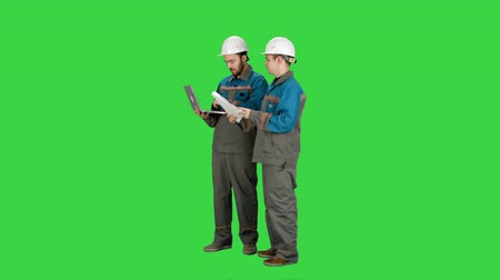 discussão : Two experienced industrial technicians work on laptop on a Green Screen, Chroma Key.
