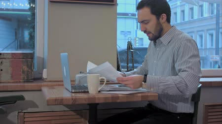 papelada : Tired young bearded businessman in a cafe prepareing for meeting. Stock Footage