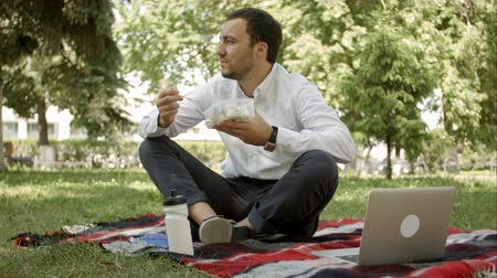 Çin yemek çubukları : young business man enjoying food which he brought in a lunch box from home. Lunchtime at the park outdoors.