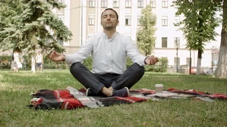 meditující : Man is meditating on green grass in the park with face raised up to sky and eyes closed on sunny summer day. Concept of meditation, dreaming, wellbeing and healthy lifestyle