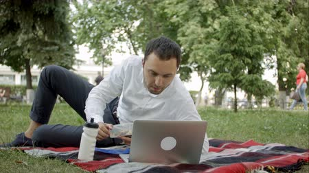 umma : Young executive working in the park on laptop, while having lunch