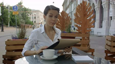peça : Elegant businesswoman calling for waiter while sitting at coffee shop, business lunch break of female executive