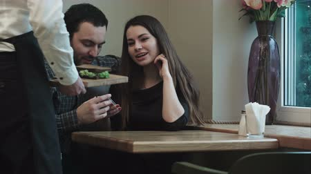 официант : Waiter brings order to couple in cafe