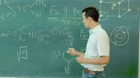 преподаватель : Chemistry teacher surrounded stands near the chalkboard in classroom